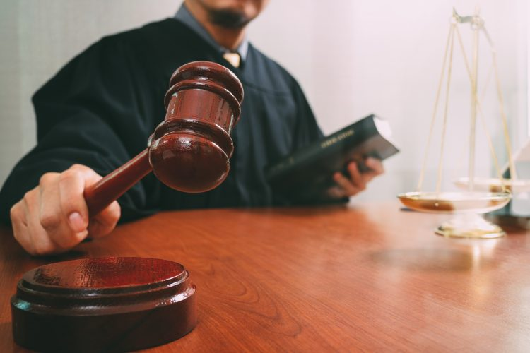 justice and law concept.Male judge in a courtroom with the gavel and working with holy book and brass scale on wood table